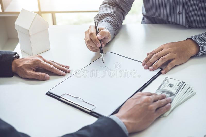 Man customer signing buying home policy document agreement, successful loan contract and salesman receive money after good deal.  royalty free stock photography
