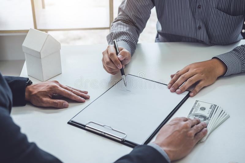 Man customer signing buying home policy document agreement, successful loan contract and salesman receive money after good deal stock images