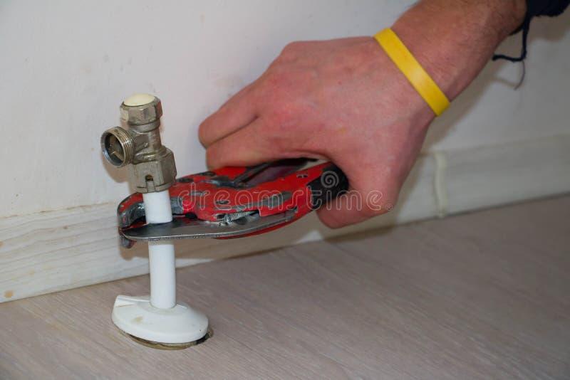 Man cut plastic pipe radiator with scissors royalty free stock photo