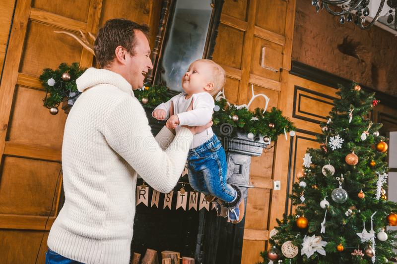 Man and cute baby are ready to celebrate new year. Happy Father And child son Near Christmas Tree And Fireplace In royalty free stock photo