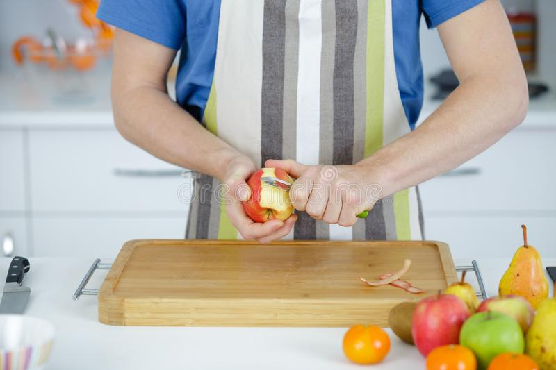 Man cuts apple on wooden table royalty free stock photos