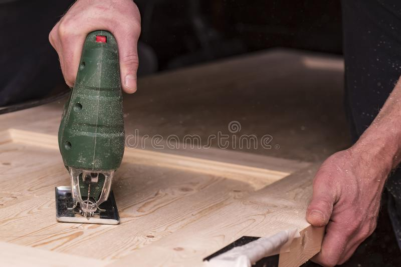 Man cuts a circle in a wooden door using an electric jigsaw joinery. Close-up royalty free stock photo