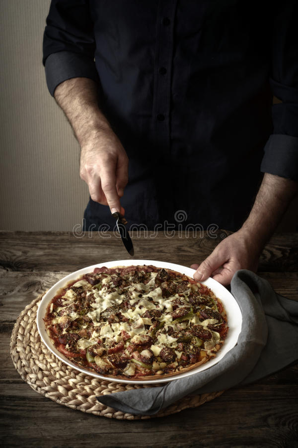 Download Man Cuts The Finished Pizza On A White Dish Stock Photo - Image: 83710939