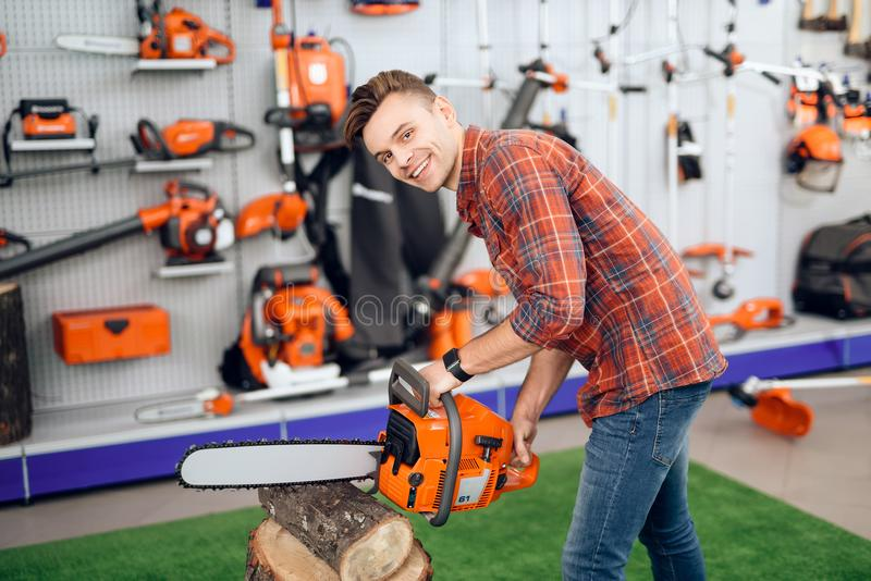 A man cuts a log in the store. The buyer checks how the chainsaw works. A young couple came to the garden tools store to buy equipment for gardening royalty free stock image