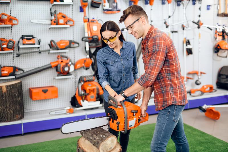 A man cuts a log in the store. The girl and the guy check how the chainsaw works. A young couple came to the garden tools store to buy equipment for gardening stock photography