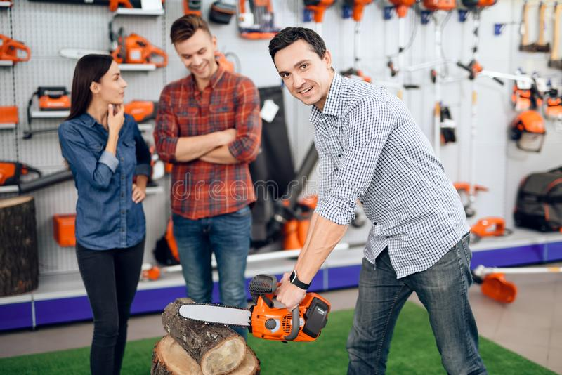 A man cuts a log in the store. A young couple came to the garden tools store to buy equipment for gardening stock image