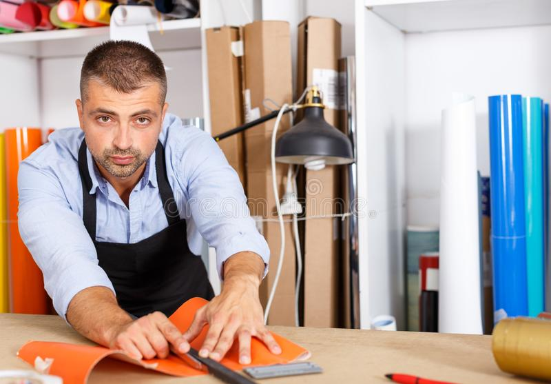 Man cuts off a piece of colored vinyl film in workplace royalty free stock photography