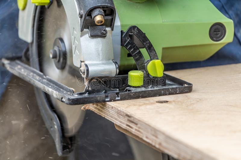 Man cuts a plywood plate using a green electric circular saw tool with yellow chips on a work bench stock photography
