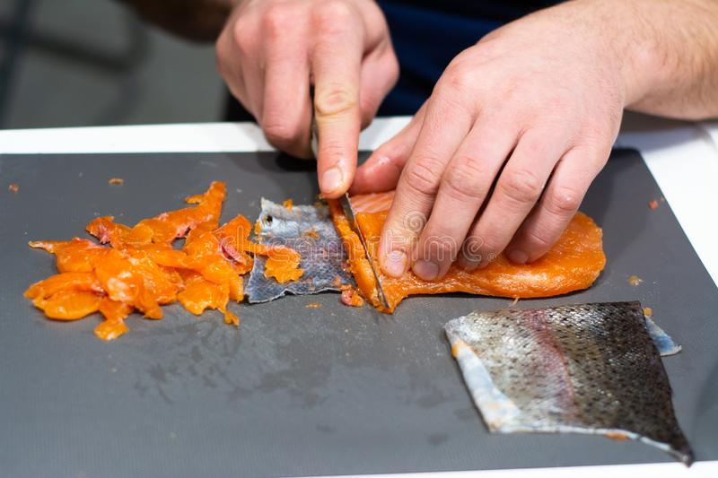 A man cuts red fish into pieces. stock image