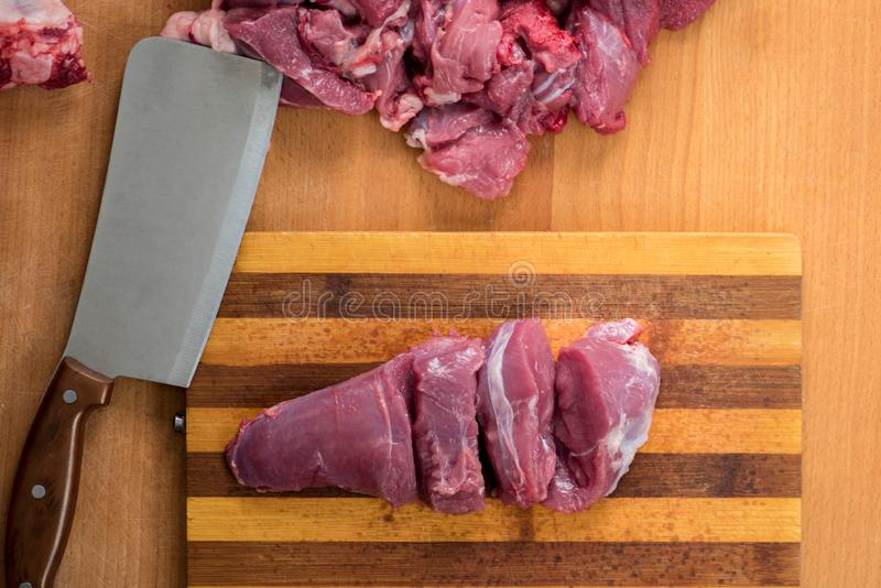 Man is cutting beef on an old board stock photography