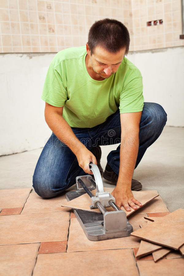 Man cutting ceramic floor tiles. Installing them in a new building stock photography