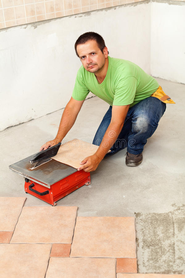 Man Cutting Ceramic Floor Tiles With Electric Cutter Stock Photo