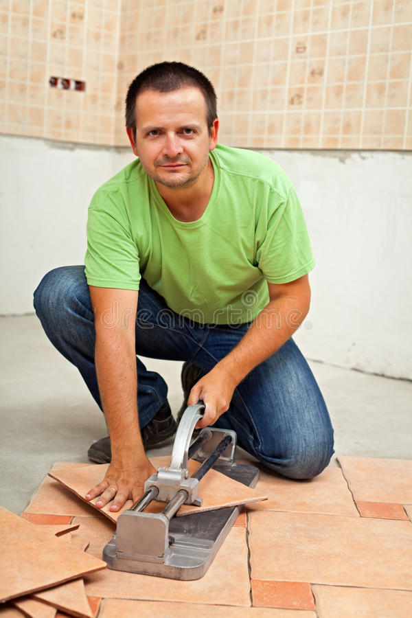 Man cutting ceramic floor tiles with manual cutter royalty free stock images