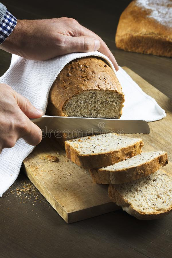 Man cutting fresh homemade bread on a table royalty free stock photos