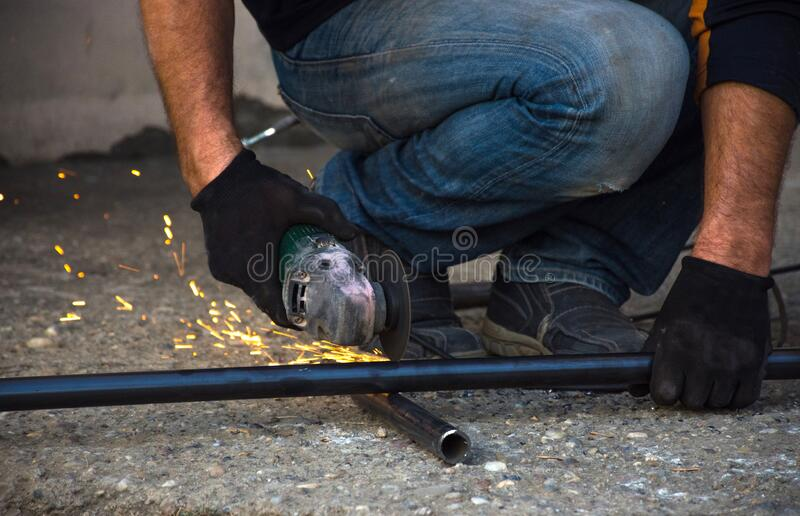 Man cutting a gas pipe for central gas installation.  stock image
