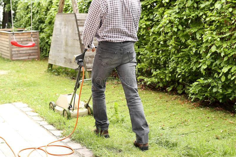 Man is cutting the grass. With an electrical cutter stock photography
