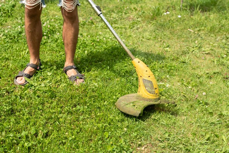Man cutting the grass in the backyard with a lawn mower, trimmer, detail. Copy space. Man cutting the grassin the backyard with a lawn mower, trimmer, detail stock images