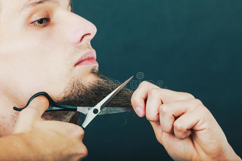 Man cutting his beard royalty free stock images