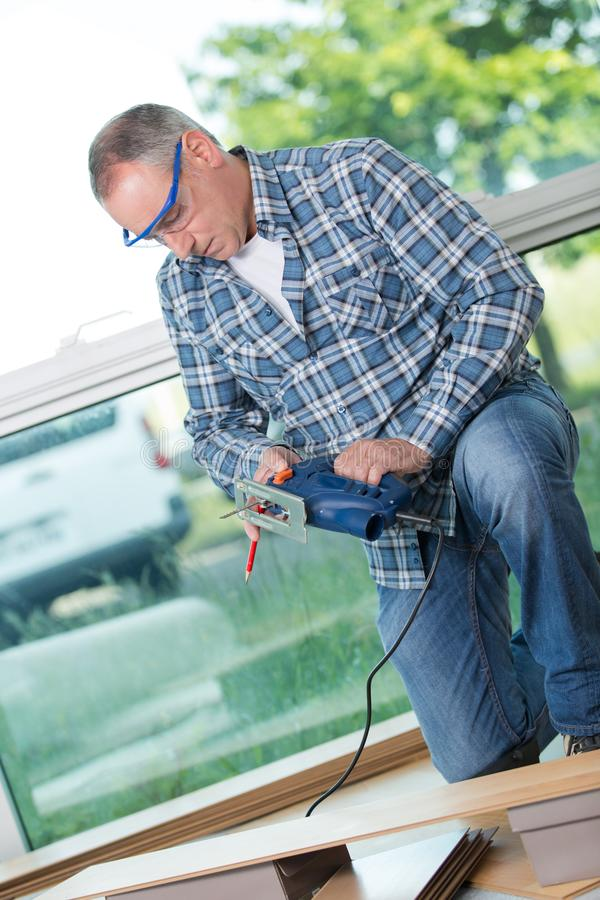 Man cutting laminate board with jigsaw. Man stock image