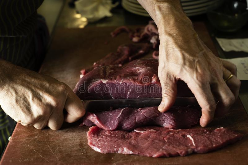 Man cutting a piece of beef in a professional kitchen royalty free stock photo