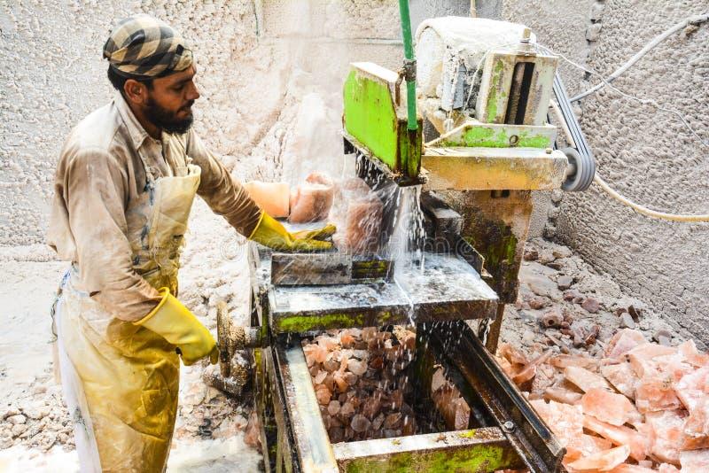 A man cutting rock salt to make tiles & bricks royalty free stock image