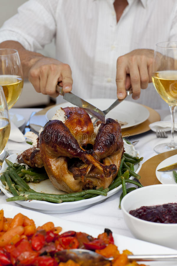 Man cutting a turkey for Christmas dinner stock photo
