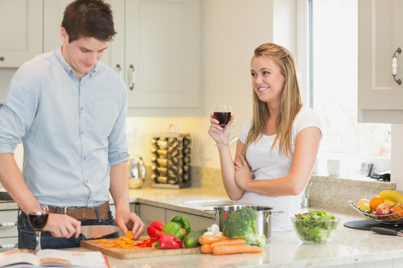 Man cutting vegetables with woman drinking wine. Man cutting vegetables with women drinking wine in kitchen stock images