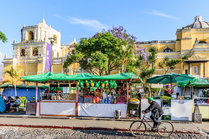 Man cycles past La Merced church & food stalls, Antigua, Guatemala royalty free stock image
