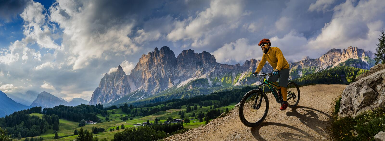 Man cycling on electric bike, rides mountain trail. Man riding on bike in Dolomites mountains landscape. Cycling e-mtb enduro stock image