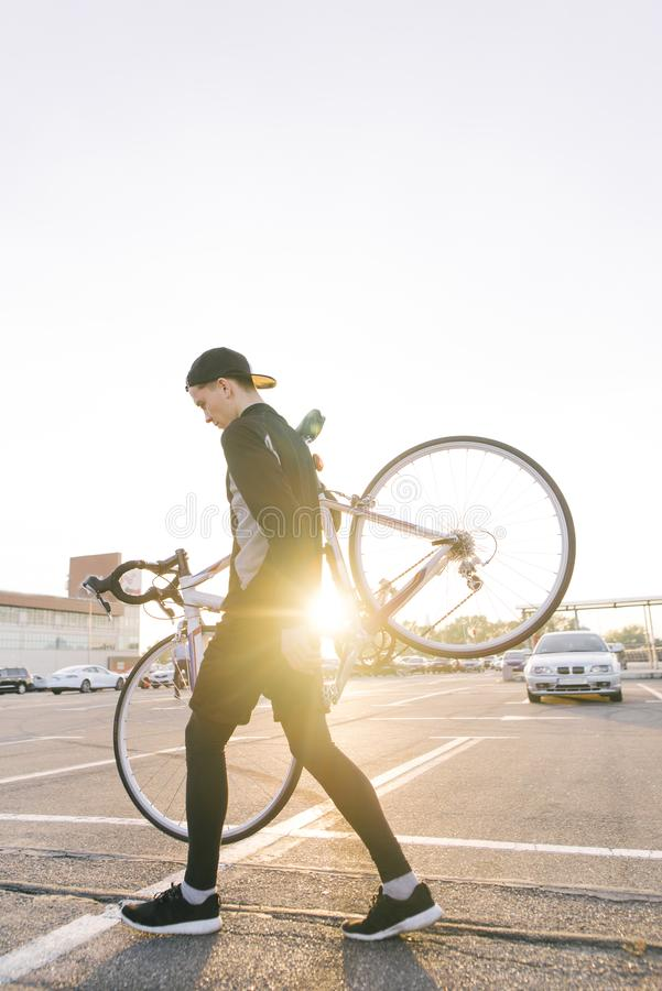 Man is a cyclist in dark sportswear, carrying a highway bike on his shoulders against the background of the sunset royalty free stock image
