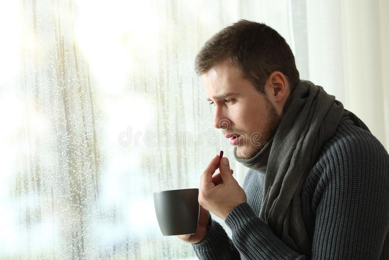 Man dåligt att ta en smärtstillande medelpreventivpiller i en regnig dag av vintern royaltyfria bilder