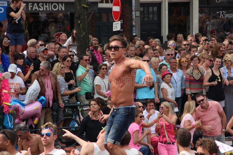 Man dancing on boat during Amsterdam gay pride canal parade. Man dances on gay pride boat as the crowd watches. Incidentally he is right underneath the no access stock photo