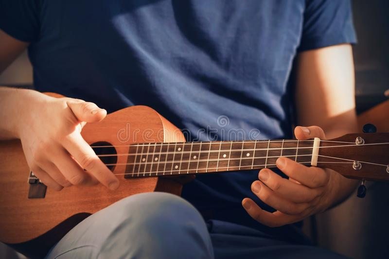 A man plays a cheerful tune on a ukulele stock images