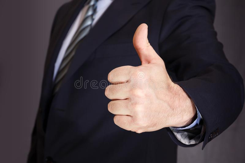A man in a dark coat holds hand with thumb up stock photography