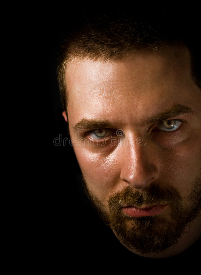 Man in the dark with evil eyes stock photography