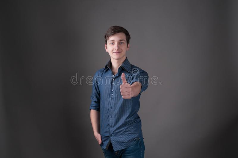 Man with dark hair in blue shirt holding hand in pocket, showing thumbs up. Handsome young man with dark hair in blue shirt holding hand in pocket, showing stock photos