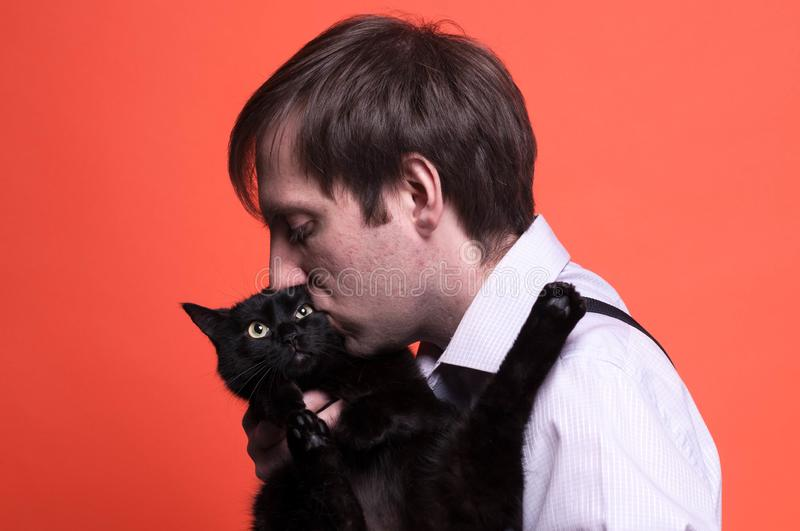 Man with dark hair and closed eyes holding and kissing muzzle cute black cat on coral background. Handsome man with dark hair and closed eyes holding and kissing royalty free stock image