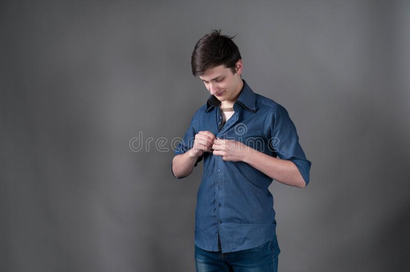 Man with dark hair fasten blue shirt. Handsome young man with dark hair fasten blue shirt and looking at chest on gray background stock image