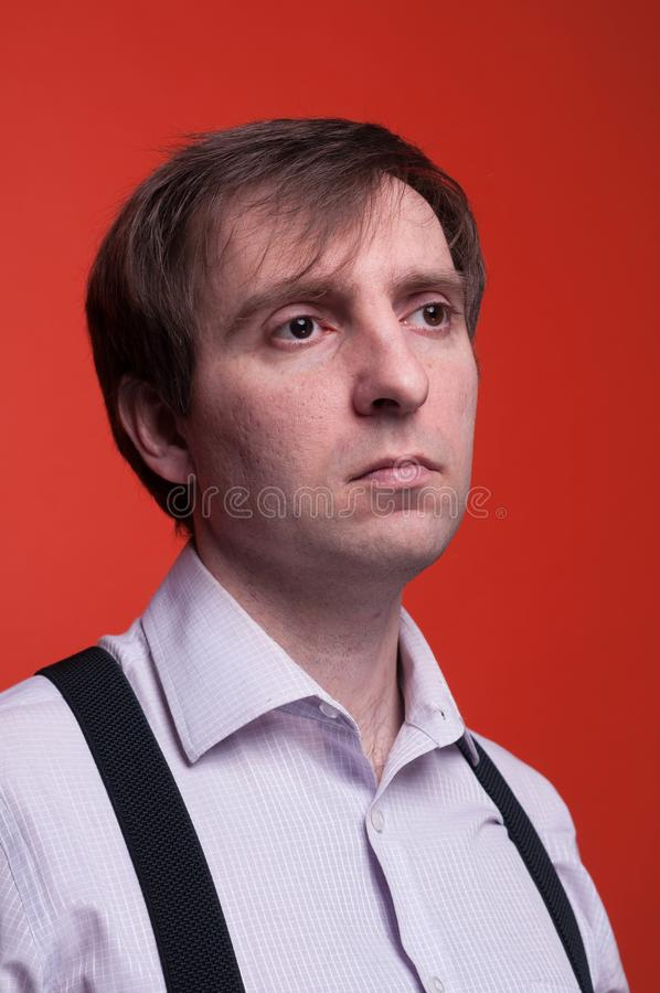 Man with dark hair in pink shirt and black suspender looking away on coral background stock photos