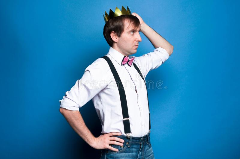 Man with dark hair in pink shirt, bow tie and black suspender holding hand on hip, correcting gold shiny crown. Side view of handsome man with dark hair in pink royalty free stock photos