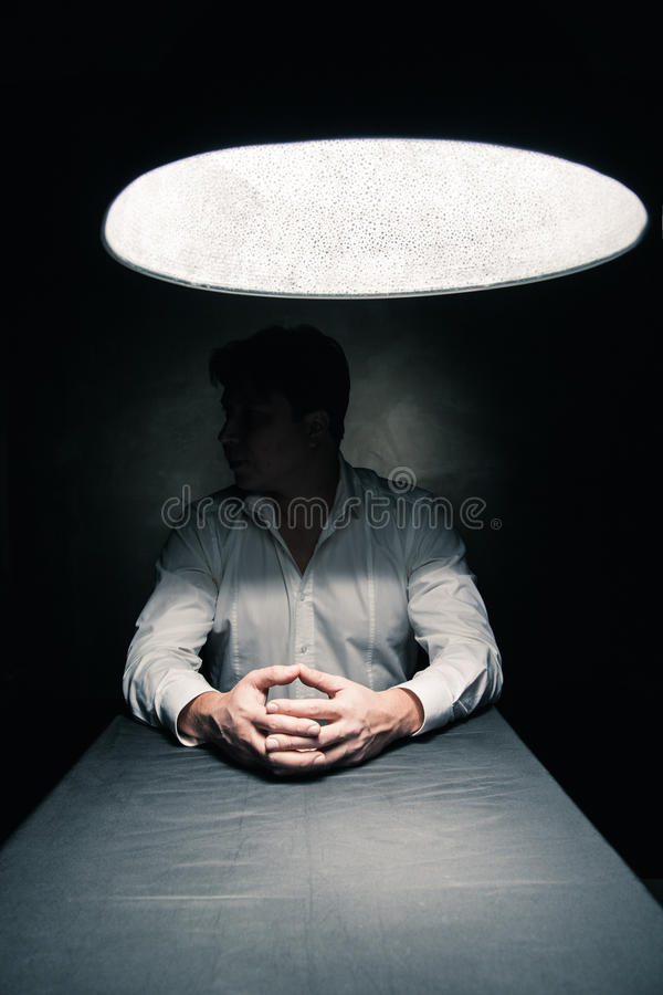 Man in a dark room illuminated only by lamp. Man in a dark room illuminated only by a light coming from a lamp no face seen royalty free stock photos