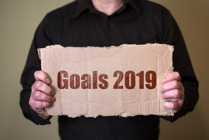 A man in a dark shirt holding a piece of cardboard with text Goals 2019 royalty free stock image