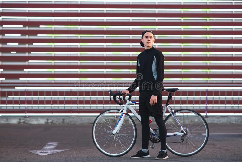 Man in dark sportswear and with a bike stands on the striped background of the big screen and looks at the camera stock photos