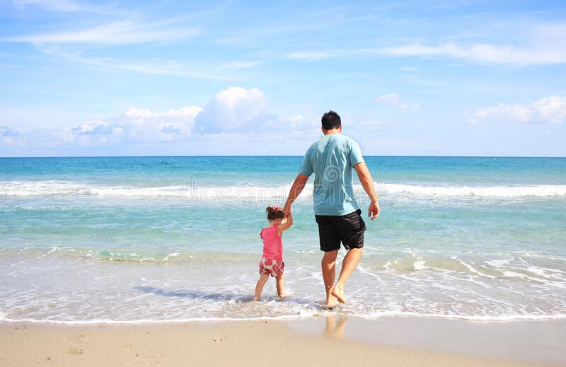 Man and daughter at beach stock images