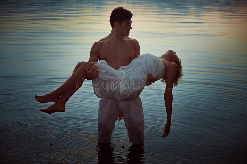 Man with dead lover in lake waters. Dark romance royalty free stock photos