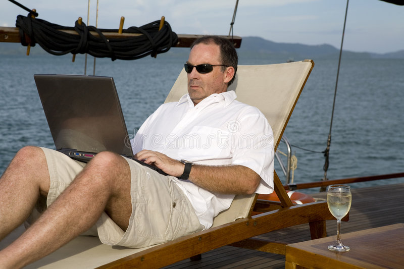 Man on deck of yacht with laptop. Handsome man on deck of yacht with laptop royalty free stock photos