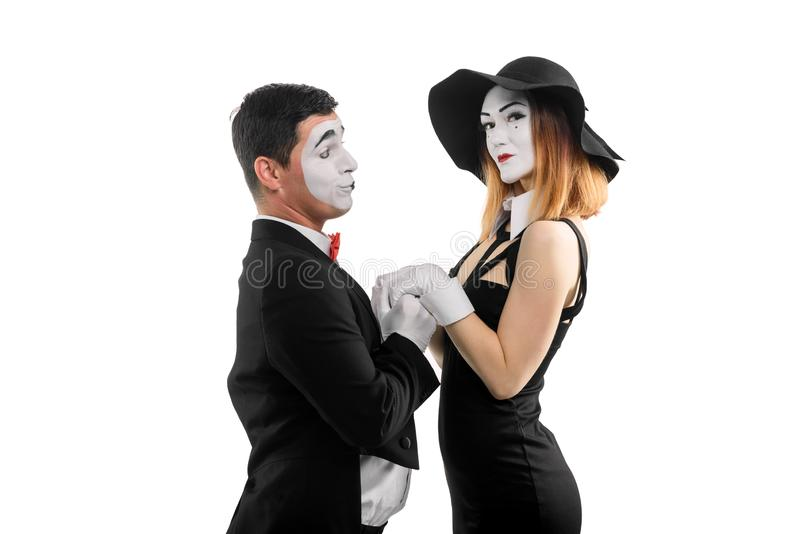 Man declaring love to woman. Dramatic sketch by couple of mime performers dressed in classic outfit, isolated on white royalty free stock photo