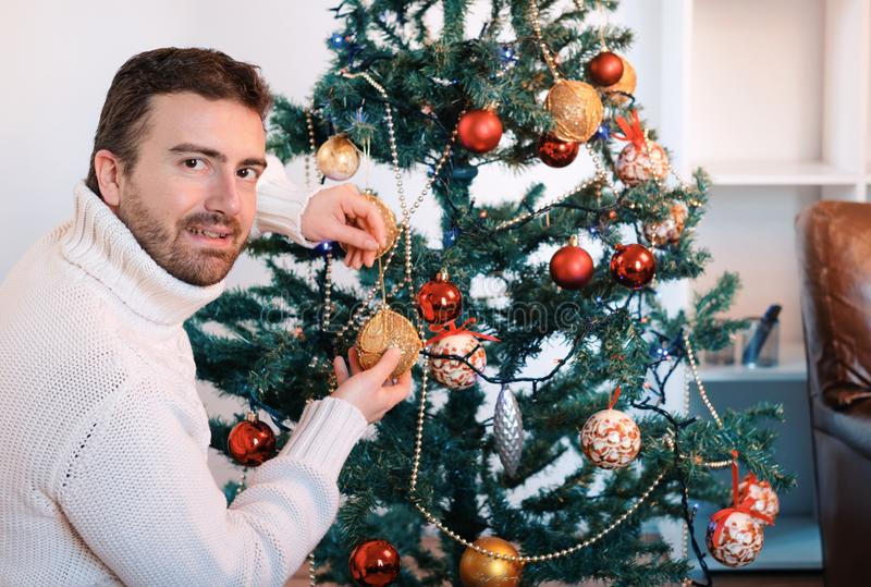 Man decorating a christmas tree with golden balls. At home stock photo