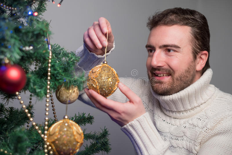 Man decorating a christmas tree with golden balls. Main focus on the man face royalty free stock images