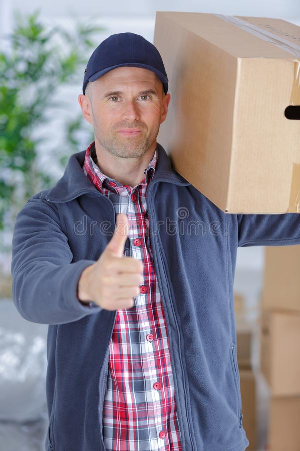 Man delivering boxes during house move. Moving royalty free stock images